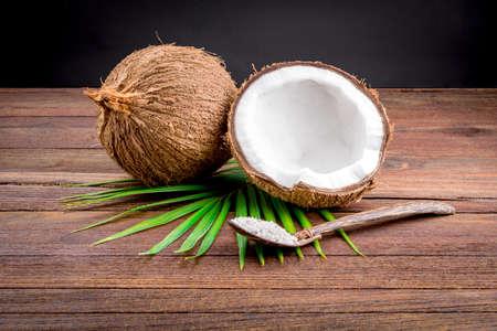 coco: Cerca de un coco y tierra copos de coco en el suelo de madera