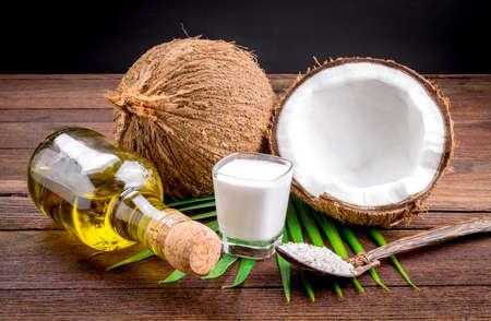coco: La leche de coco y el aceite de coco en la mesa de madera Foto de archivo