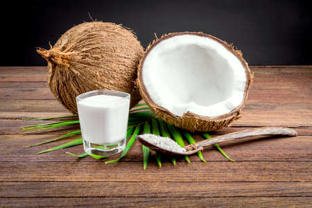 Coconut and coconut milk in glass on wooden table Stock Photo