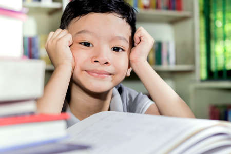 boy book: young asian boy with book in Library.