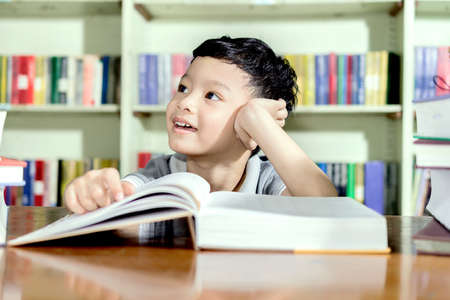 young asian boy with book in Library.