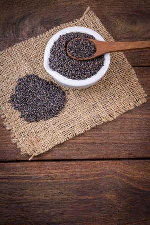 serine: Heap of black Sesame (close-up shot) on wooden background