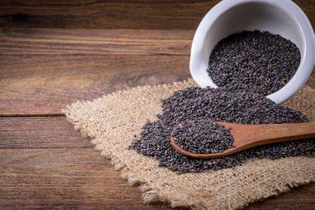 Heap of black Sesame (close-up shot) on wooden background