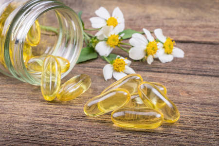 primrose oil: Closeup the yellow soft gelatin supplement fish oil capsule on wooden Stock Photo
