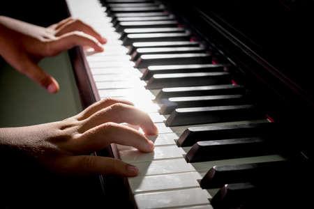 piano: Primer plano de las manos del niño tocando el piano