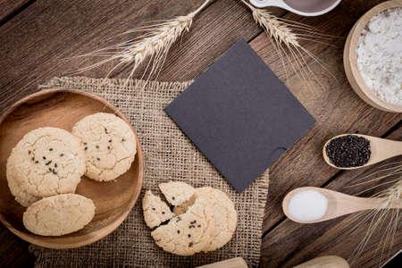 古い空白用紙 1 枚、クッキーの材料を焼くと調理器具周辺農村のビンテージ木製キッチン テーブル。無料レシピのテキスト領域と背景。
