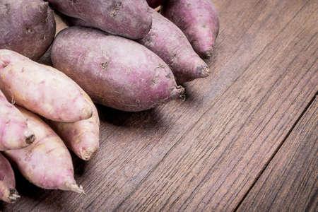 batata: Las patatas dulces hermosas sobre una mesa de madera. Foto de archivo