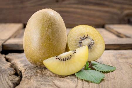 kiwi fruta: Su conjunto y los kiwis de oro cortadas en la tabla de cortar de madera