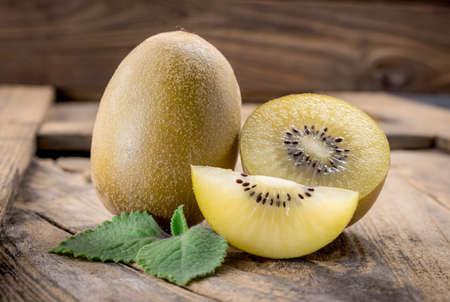 kiwi fruta: Whole and cut golden kiwifruit on wooden cutting board