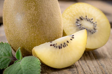 sliced fruit: Whole and cut golden kiwifruit on wooden cutting board