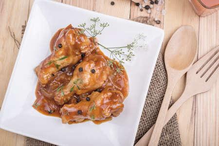 fine legs: Baked chicken in tomato sauce on wooden
