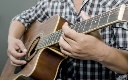 chord: Acoustic guitar being played, Fingers holding a chord.