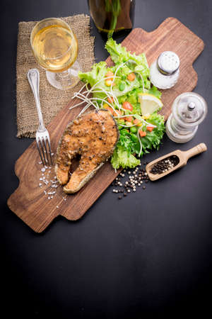 gill: salmon steak with vegetables on woodden board. Stock Photo