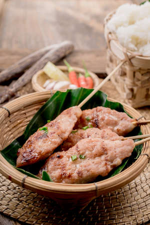 grilled pork with sweet spicy sauce and sticky rice on wooden plate: Thai street food style