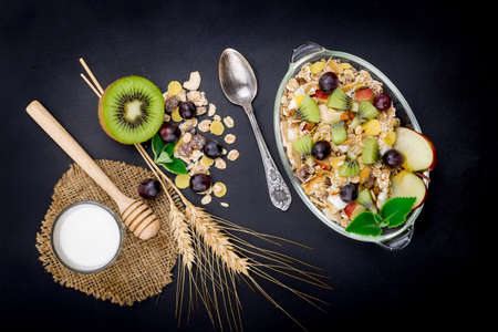 Healthy bowl of muesli, fruit, nuts and milk for a nutritious breakfast on black background.