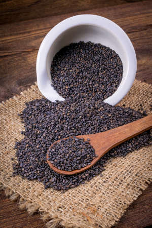 serine: Heap of black Sesame (close-up shot) on wooden background