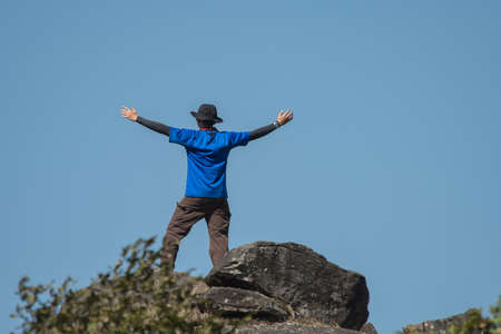 soulfulness: Young successful man open arms on mountain peak above the forest.Thailand