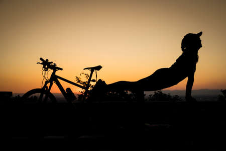 composure: Young women is engaged in yoga on sunset with bike Stock Photo