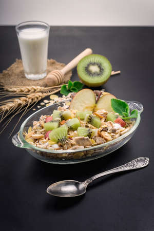 energizing: Healthy bowl of muesli, fruit, nuts and milk for a nutritious breakfast on black background.
