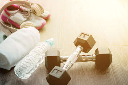 Exercise weights - iron dumbbell with extra plates on a wooden deck, Sport equipment. Sneakers, water, towel, earphones and phone on wooden background