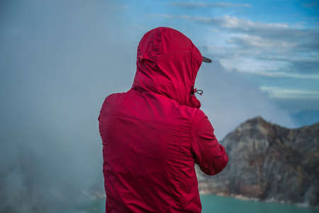 crater lake: Male photographer with backpack standing on top of a mountain and enjoying sunrise, Colorful Kawah Ijen volcano crater lake Stock Photo