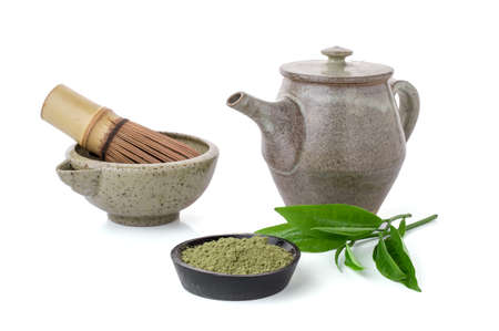 Matcha green tea in a bowl and bamboo whisk isolated Matcha is a powder of green tea leaves packed with antioxidants on white background.
