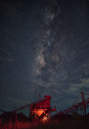 sand quarry: Crushing machine construction industry with the milky way background, Thailand.