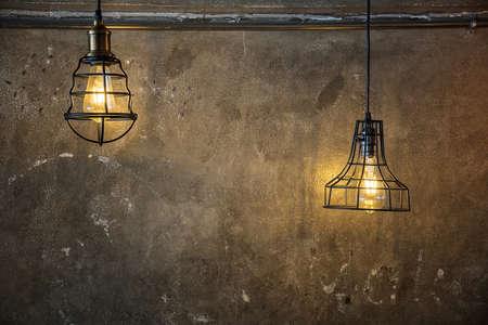 Illuminated retro style light bulbs. Trendy design, Beautiful hanging light bulbs on Plaster wall background for wallpaper Stock Photo