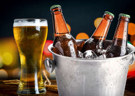 cold bottles of beer in bucket with ice in a restaurant setting Stock Photo