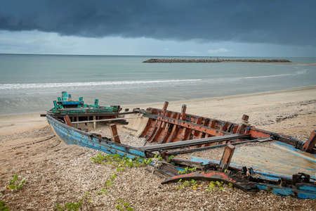 A old abandoned fishing boat and colorful sky In Thailand, Old and broken wooden boat stranded on the sandy beach