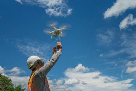 Ingeniero joven utiliza drones al aire libre con hermoso cielo con nubes, el hombre que sostiene el Drone Foto de archivo - 88789607