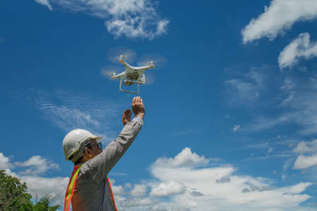 Young engineer use drones outdoor with beautiful sky with clouds, the man holding Drone Stock Photo