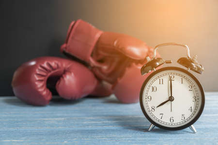 Alarm clock and boxing gloves on wooden table