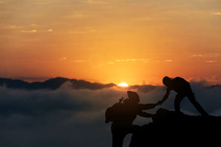 Two friends helping each other and with teamwork trying to reach the top of the mountains during wonderful summer sunset.