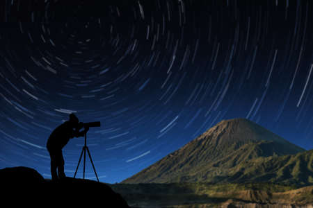 silhouette of a photographer who shoots star trail on background. Stock Photo