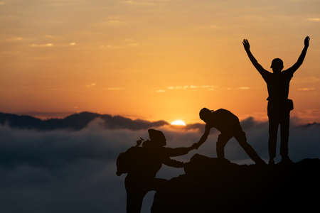friends helping each other and with teamwork trying to reach the top of the mountains during wonderful summer sunset.