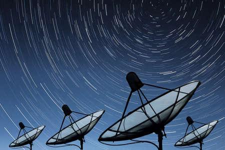 Big black Satellite Dish on star trail sky background Foto de archivo