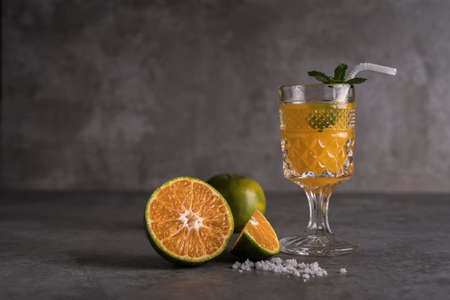 Fresh orange fruits and juice on stone table with copy space