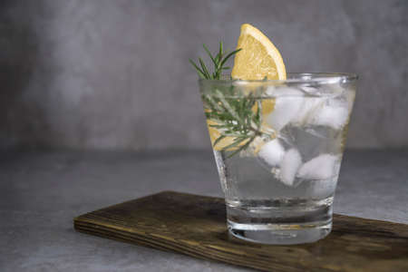 Alcoholic drink gin tonic cocktail with lemon, rosemary and ice on table. Stock Photo