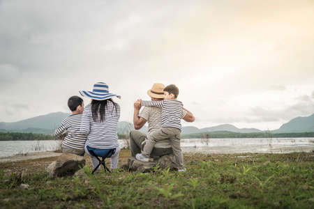 Parent with young daughters and son on picnic near the lake. Family Concepts