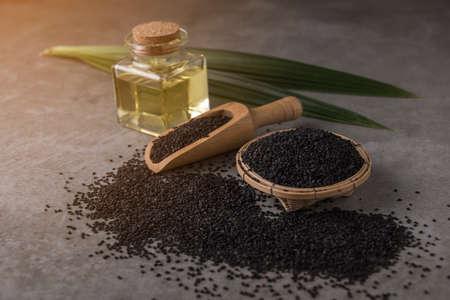 Black sesame seeds with oil on dark background.