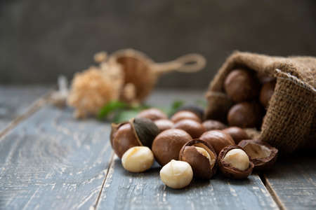 Organic Macadamia nut on wooden table - vintage filter, Closeup view of natural macadamia oil and Macadamia nuts on wooden board. Healthy product Stock Photo