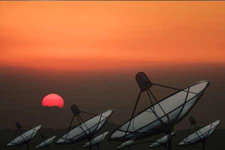 Grande antenne parabolique noire sur fond de coucher de soleil.