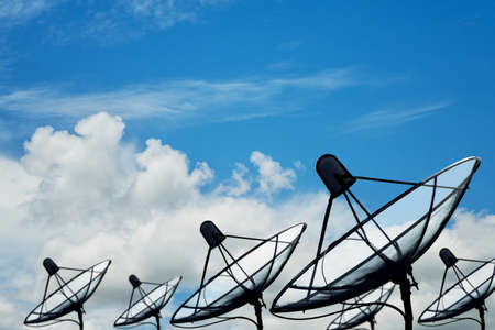 Big black satellite dish on blue sky clouds background, transmission data. digital technology blue background