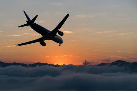 Airplane over the clouds, The plane on a background of during sunset. Reklamní fotografie