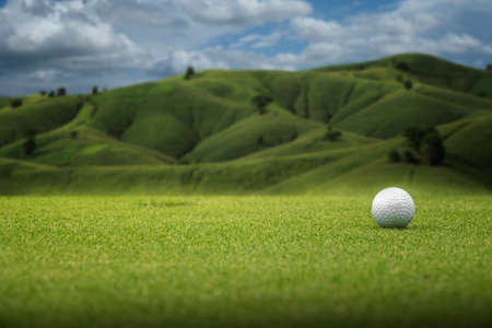 Golf ball on the green at mountain background and beautiful sky