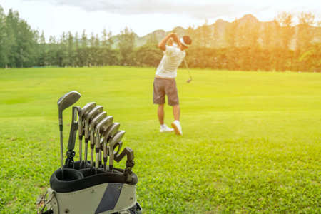 Golf clubs drivers over green field, Golfer hitting golf shot with club on course at evening time.