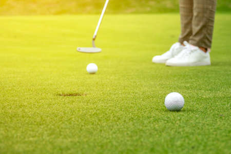Golfer putting golf ball on the green golf, lens flare on sun set evening time. 写真素材