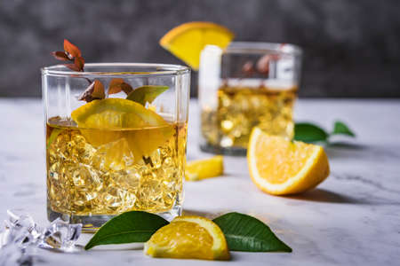 Fresh cocktail with orange, mint and ice, selective focus, Glass of the orange alcoholic drink with ice and slice of orange peel on the dark background.