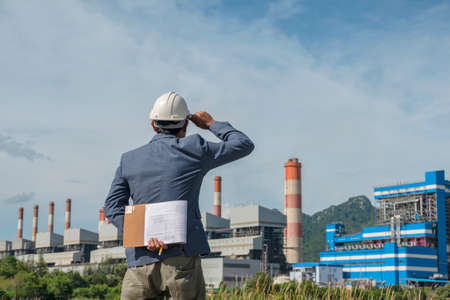 Businessmen at power plant background, safety helmet for safety concept and power plant project site background.